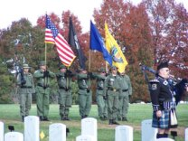 Bagpiper and color guard at a veteran's funeral.