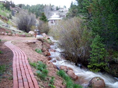 Brick walkway and trout stream alongside the cottages lead to large gazebo and outdoor kitchen area.